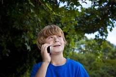 Young boy talking on a cell phone. Stock Photos