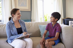 Young Boy Talking With Counselor At Home Stock Photography