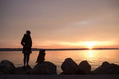 Young boy talking with his mother silhouetted against an orange. Young boy talking with his mother silhouetted against a glowing orange marine sunset reflected Royalty Free Stock Photos