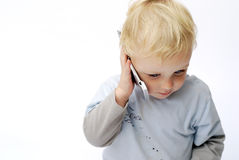 Young boy talking on mobile phone. Cute young boy talking on mobile cellular phone against white background Royalty Free Stock Photos