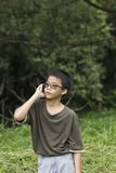 Young boy talking on the phone. Asian Thai young boy talking on mobile phone outdoor Stock Photo