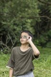Young boy talking on the phone. Asian Thai young boy talking on mobile phone outdoor Stock Photos