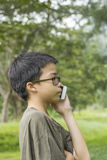 Young boy talking on the phone. Asian Thai young boy talking on mobile phone outdoor Royalty Free Stock Image