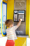 Young boy talking to the phone in a booth Royalty Free Stock Photography