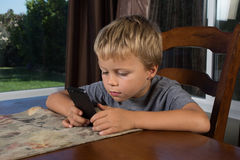 Young Boy Texting on Phone Royalty Free Stock Photo