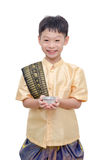 Young boy in Thai traditional dress holding water cup Stock Image