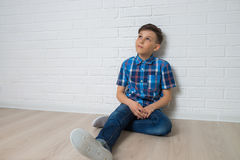 Young boy thinkin sitting near white white brick wall looking up, copy space available. stock image