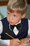 Young boy thinking in classroom. Young boy thinking about lesson in classroom Royalty Free Stock Photos