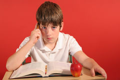 Young boy thinking at desk Stock Photos