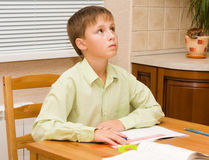 Young boy thinking,  doing his homework. Young Boy doing his homework at home Stock Photography