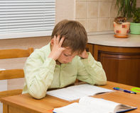 Young boy thinking,  doing his homework. Young Boy doing his homework at home Royalty Free Stock Image