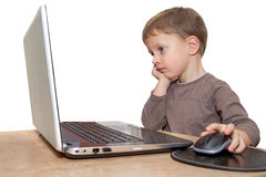 Young boy thinking in front of laptop Royalty Free Stock Photo