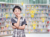 Young boy thinking with light bulbs in library Royalty Free Stock Photos