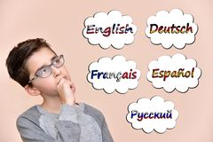 Young boy thinking which languages to learn. Thoughtful young boy thinking which languages to learn. Five different languages in the thought bubbles stock images