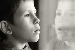 Young boy in thought with window reflection. Contemplating young boy in thought with window reflection