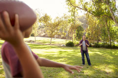 Young boy throwing American football to his dad in park Royalty Free Stock Image
