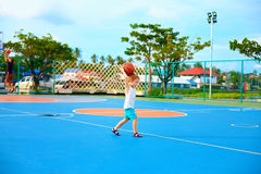 Young boy throwing ball, playing basketball on playground Stock Photos