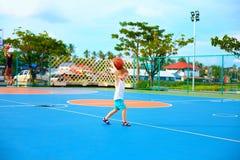 Young boy throwing ball, playing basketball on playground Stock Photos