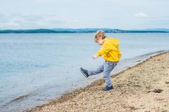 Young boy throwing stones in sea water.  Royalty Free Stock Photo