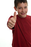 Young boy with thumb up 2. Young boy smiling, with thumb up, focus on his hand and thumb, isolated on white Royalty Free Stock Image