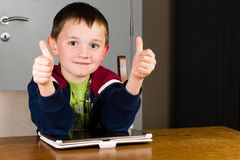Young boy thumbs up. Little boy giving thumbs up while using his tablet computer at the living room table Royalty Free Stock Photos