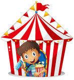A young boy with a ticket and a popcorn near the tent Royalty Free Stock Photo