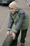 Young Boy With Tire. A young boy rolls a tire down a sidewalk in Winter Stock Photography