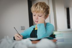 Young boy tired stressed of writing, doing homework royalty free stock image