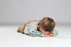 Young boy toddler. Tired toddler boy lying on the ground with his face down Royalty Free Stock Image