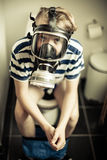 Young boy on toilet wearing gas mask. Three quarter body portrait of young boy sat on toilet wearing gas mask for the smell, sepia tone Stock Photos