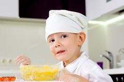 Young boy in a toque learning how to cook Stock Photography