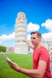 Young boy with toristic map on travel to Pisa. Tourist traveling visiting The Leaning Tower of Pisa. Royalty Free Stock Photography