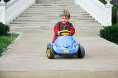 Young boy in toy car Stock Image