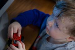 Young boy with toy. Young boy playing with red toy royalty free stock photos