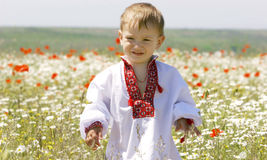 Young boy in traditional clothes. In flowers Stock Image