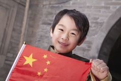 Young Boy in Traditional Courtyard with Chinese Flag Royalty Free Stock Image