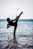Young boy training karate in sea Royalty Free Stock Image