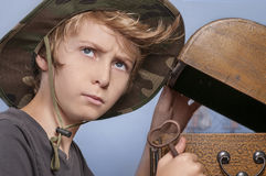 Young boy and  a treasure chest. Young boy in a traveler hat opening a treasure chest and holding a key looking thoughtfully Royalty Free Stock Images