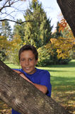 Young boy by a tree in autumn Royalty Free Stock Photos