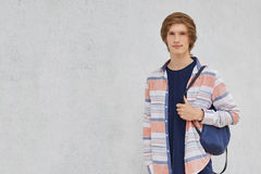 Young boy with trendy hairdo wearing casual shirt holding rucksack on his back standing against grey concrete wall with copy space royalty free stock photos