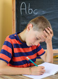 Young boy tries to do his homework royalty free stock photo