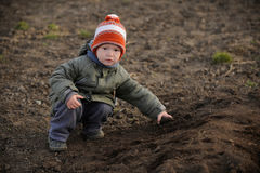 A young boy tries to help his parents. Plant potatoes in a vegetable garden in the village stock photo