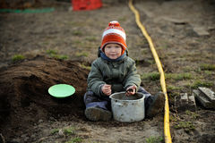 A young boy tries to help his parents. Plant potatoes in a vegetable garden in the village stock image