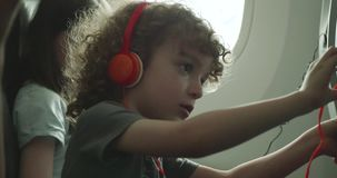 Young boy trying to adjust his seat back enterntaiment device on an aeroplane. Young boy wearing headphones trying to adjust his seat back entertainment device stock video