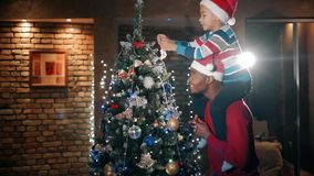 A child is decorating a christmas tree with new year`s toys, sitting on his father`s shoulders.