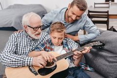Young boy trying to learn playing guitar while his father and grandpa are. Helping him stock photography