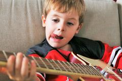 A young boy trying to play guitar. Focus on the face of the child with a blurry foreground. Royalty Free Stock Photos