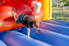 Young boy tumbling around on a jumping castle. Young boy tumbling around on an inflatable plastic jumping castle in a kids playground or at an annual fair Stock Photo