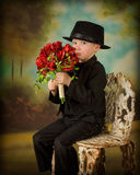 Young boy in tuxedo 2. Little boy in tuxedo with bouquet of roses pouting Royalty Free Stock Photos