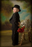 Young boy in tuxedo. Little boy in tuxedo with bouquet of roses Royalty Free Stock Photography